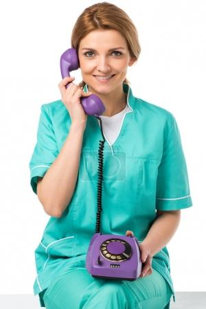 portrait of smiling veterinarian talking on telephone isolated on white
