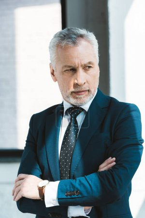 Photo for Portrait of confident senior businessman standing with crossed arms and looking away - Royalty Free Image