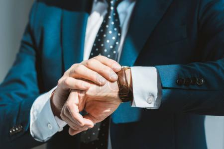 close-up partial view of businessman in formal wear checking wristwatch