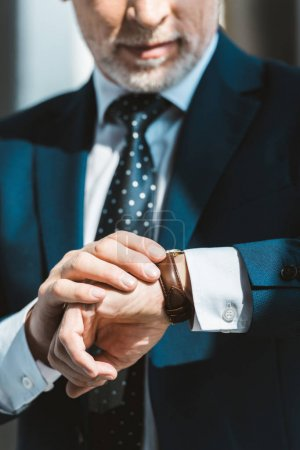 Photo for Cropped shot of senior businessman in formal wear checking wristwatch - Royalty Free Image
