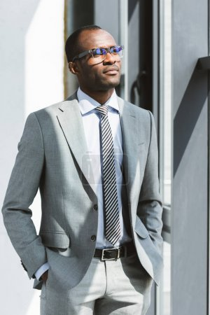 confident young african american businessman in eyeglasses standing with hands in pockets and looking away