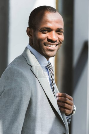 portrait of handsome young african american businessman adjusting suit jacket and smiling at camera