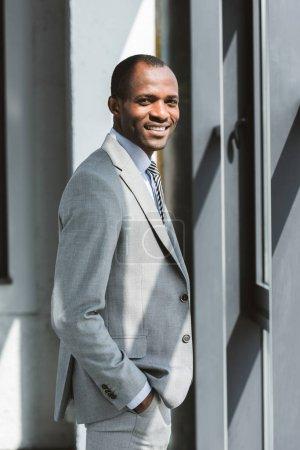 Photo pour Portrait de beau jeune entrepreneur africain-américain debout main dans la poche et souriant à la caméra - image libre de droit