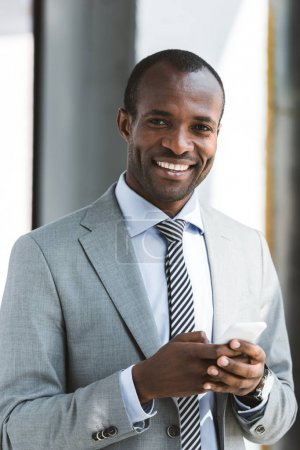 portrait of handsome young african american businessman using smartphone and smiling at camera