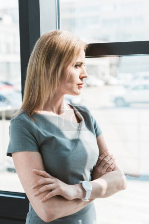 side view of beautiful confident businesswoman standing with crossed arms and looking at window