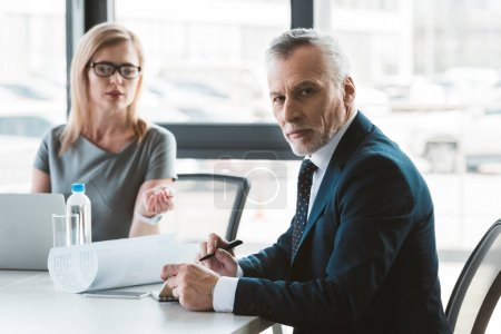 serious senior businessman looking at camera while having discussion with female colleague