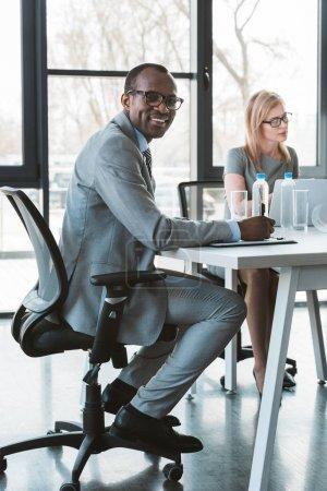 Photo pour Bel homme d'affaires afro-américain dans lunettes souriant à la caméra tout en travaillant avec une collègue au bureau - image libre de droit