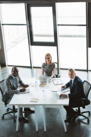 high angle view of professional multiethnic business people smiling at camera while sitting together at business meeting