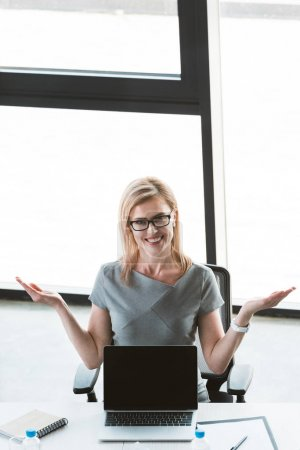 high angle view of cheerful businesswoman in eyeglasses showing laptop with blank screen