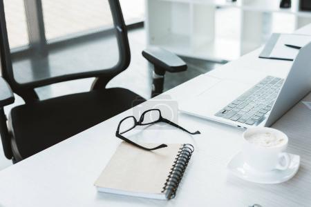 close-up view of eyeglasses, notebook, cup of coffee and laptop on table in office