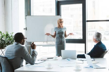 Foto de Hermosa empresaria sonriente, de pie junto a la pizarra y mirando a sus colegas durante la reunión de negocios - Imagen libre de derechos