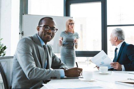 Foto de Joven empresario afroamericano tomando notas y sonriendo a cámara teniendo conversaciones con colegas en reuniones de negocios - Imagen libre de derechos