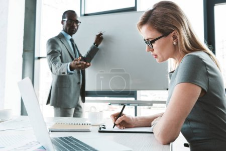 african american businessman pointing at whiteboard and looking at female colleague taking notes during meeting
