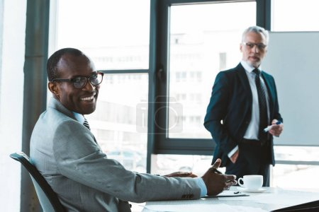 handsome african american businessman in eyeglasses smiling at camera while working with male colleague in office