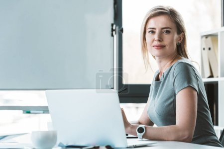 attractive businesswoman using laptop and smiling at camera
