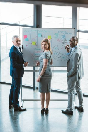multiethnic business people smiling at camera while working at whiteboard with graphs and charts