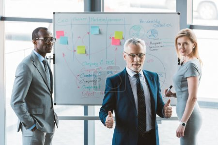 senior businessman in eyeglasses showing thumbs up and smiling at camera while working with colleagues at whiteboard