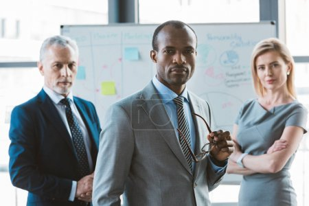 confident african american businessman holding eyeglasses and looking at camera while business colleagues standing near whiteboard behind