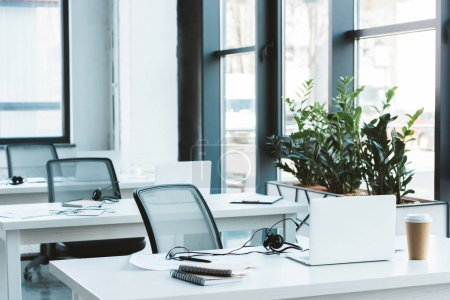 headsets and laptops on tables in modern office