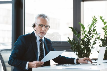 serious businessman in eyeglasses and headset using laptop and looking at camera