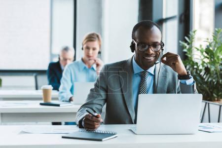 Photo pour Beau sourire africain-américain homme d'affaires dans les lunettes et le casque à l'aide d'ordinateur portable et prendre des notes - image libre de droit