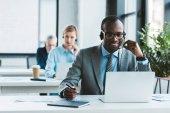beau sourire africain-américain homme d'affaires dans les lunettes et le casque à l'aide d'ordinateur portable et prendre des notes
