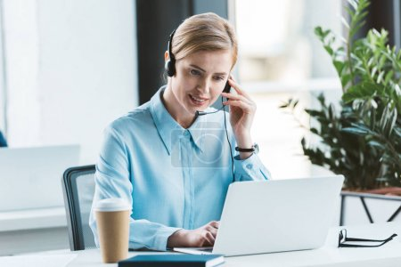 smiling businesswoman in headset using laptop in office