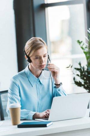 businesswoman in headset using laptop in office