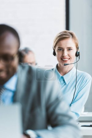 selective focus of beautiful businesswoman in headset smiling at camera