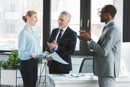 happy multiethnic businessmen applauding to cheerful businesswoman in office