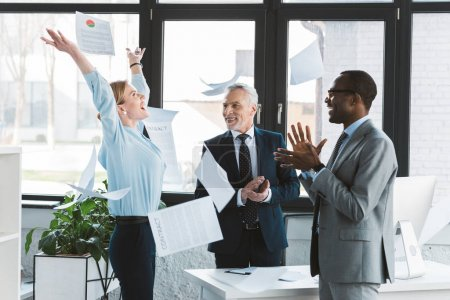 excited multiethnic business people applauding and throwing papers in office