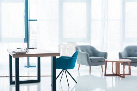 wooden table and empty cozy armchairs in modern office interior