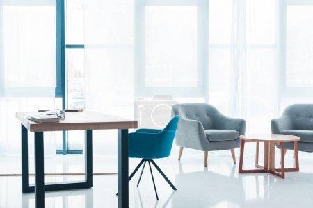 Photo pour Table en bois et fauteuils confortables vides dans l'intérieur de bureau moderne - image libre de droit