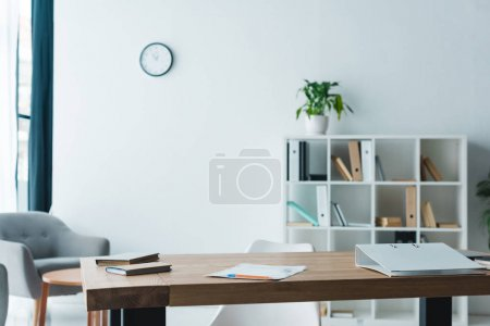 wooden table with folder, books and papers in modern office