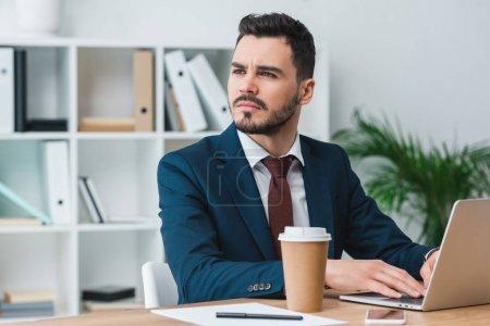 Photo pour Beau jeune homme d'affaires à l'aide d'ordinateur portable et à la recherche de suite au bureau - image libre de droit