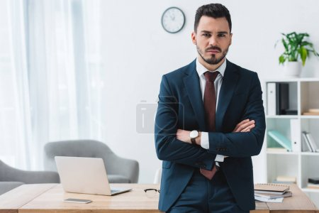 confident young businessman standing with crossed arms and looking at camera in office