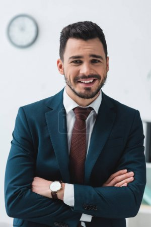 Photo for Portrait of handsome young businessman with crossed arms smiling at camera - Royalty Free Image