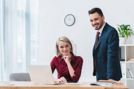 Photo pour Beaux jeunes gens d'affaires travaillant ensemble et en souriant à la caméra - image libre de droit