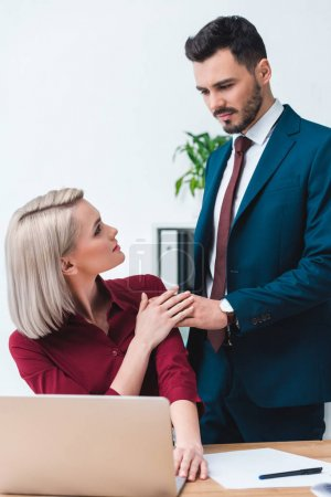 young male and female business colleagues holding hands and looking at each other in office