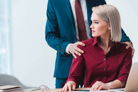 cropped shot of businessman flirting with beautiful young female colleague in office