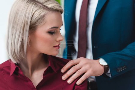 cropped shot of businessman flirting with beautiful young female colleague at workplace