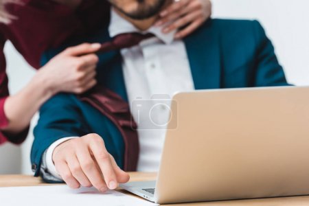 close-up view of laptop and business colleagues flirting behind