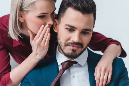 businesswoman whispering something to handsome young businessman at workplace