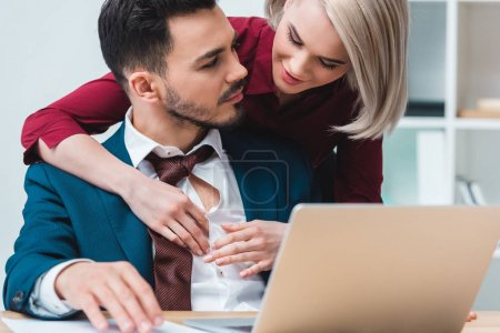 beautiful young business colleagues flirting while working together in office