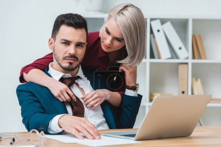 beautiful young businesswoman flirting with handsome businessman in office