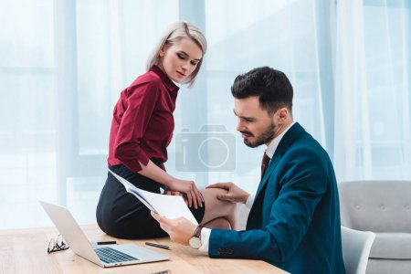 young businessman holding papers and touching knee of beautiful young female colleague