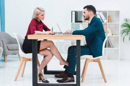 side view of young couple of business people looking at each other while working together and flirting under table in office