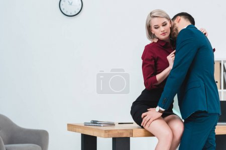 seductive young couple of business people flirting in office