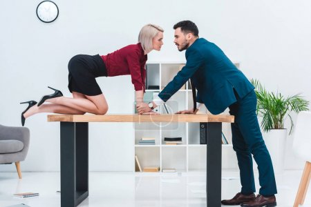 Photo for Side view of seductive young couple looking at each other while flirting in office - Royalty Free Image