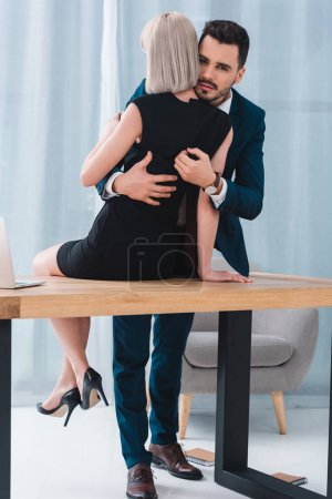 businessman and businesswoman hugging in foreplay at workplace